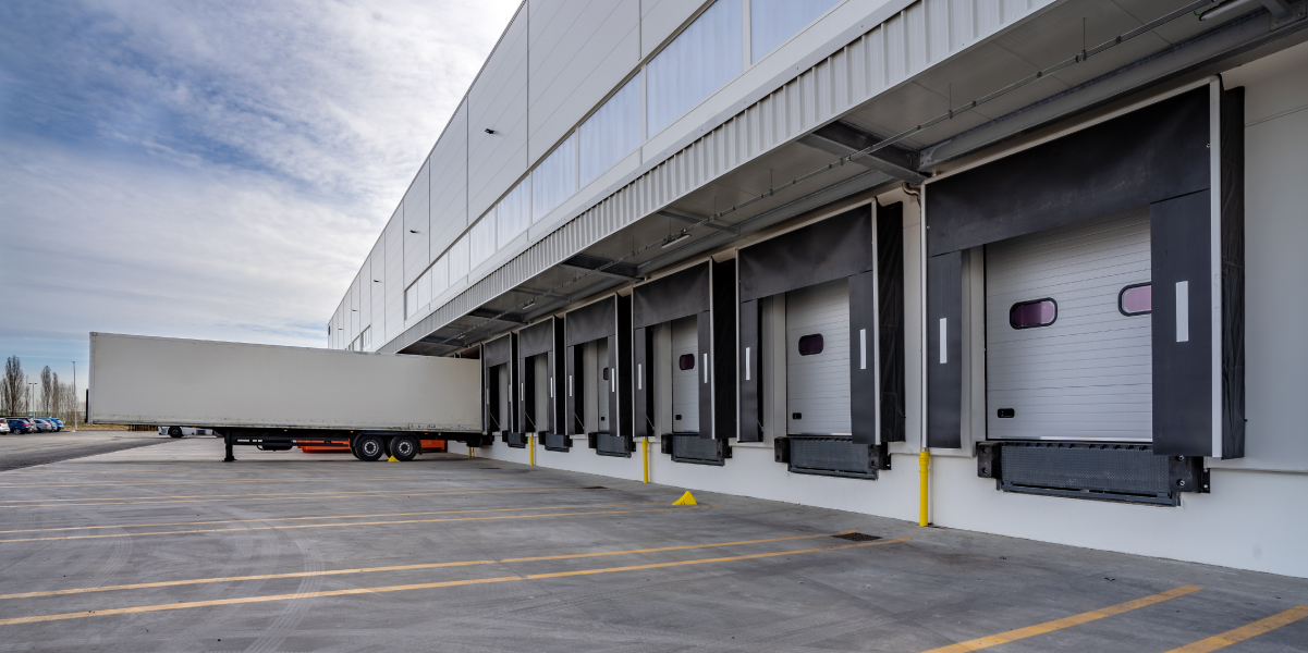 Row of loading docks at commercial warehouse building with white semi truck
