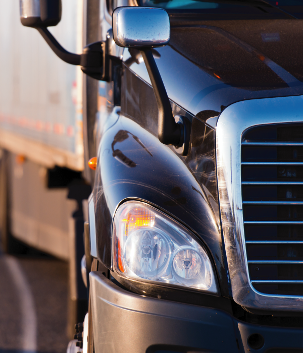 Close up details of black semi truck on the road on blurred trailer background
