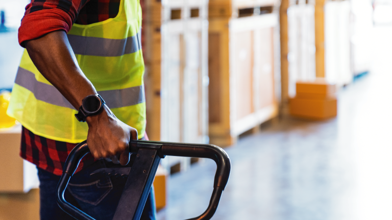 Close up of warehouse worker's hand holding hand pallet jack in distribution warehouse