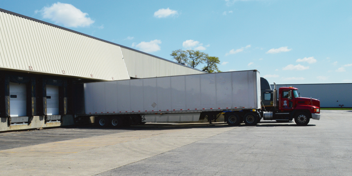 A red and a white truck at a freight loading dock with blue sky and clouds overhead