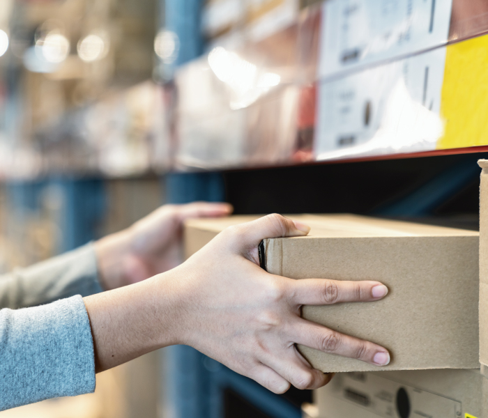 Woman's hand in self picking box and collecting product from shelf in warehouse