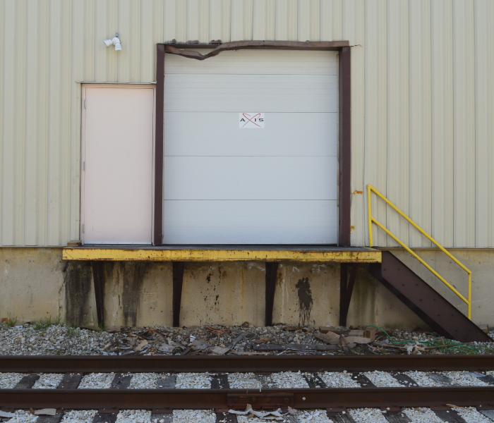 Warehouse Dock with Axis Warehouse logo located above Rail Line for Rail Car Transloading