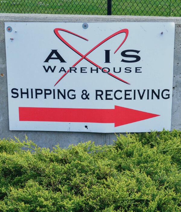Axis Warehouse Shipping & Receiving Sign Above Green Shrub